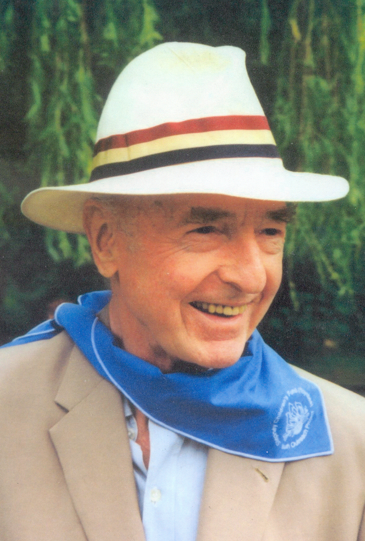 A photograph of John Profumo in a hat and scout scarf with the Stepney Children's Fund logo on